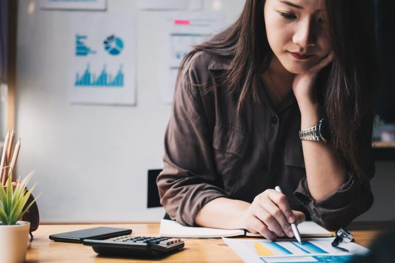 Woman sitting down with calculator and papers and working on taxes